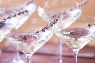 Glasses of with white champagne decorated with lavender on blurred background. DOF